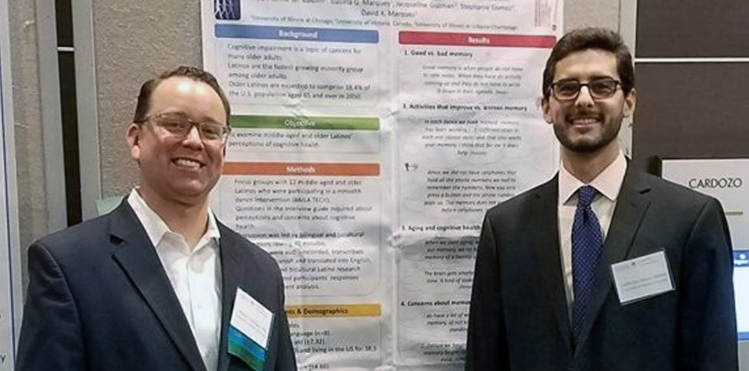 two men standing in front of a research poster
