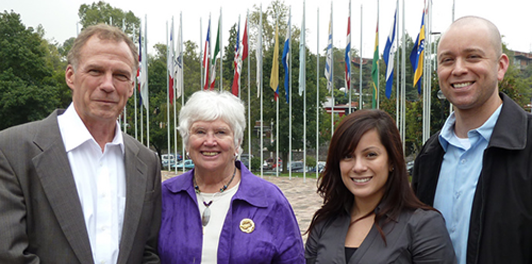 four people smiling at camera in front of a group of flags